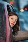 Attention to the road. A young woman looks out of the car stock photography