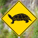 Attention Turtles Crossing animal road sign. Animal Road Sign - Attention Turtles Crossing - on blurry forest background royalty free stock images