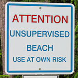 An attention unsupervised beach use at own risk sign royalty free stock photos