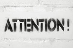 Attention. Word textured stencil print on the white brick wall stock image