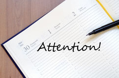 Attention write on notebook Royalty Free Stock Photo