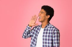 Attention! Young guy in checkered shirt holding hand near mouth. Over pink background stock image