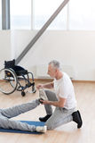 Attentive aged orthopedist helping the disabled patient in the gym. Doing my responsibilities properly. Serious skilled powerful orthopedist helping the invalid Stock Photography