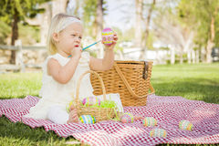 Attentive Baby Girl Coloring Easter Eggs on Picnic Blanket Stock Photo