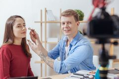 Attentive beautician giving recommendations to his video viewers. Recommendations. Smart experienced cheerful beauty blogger looking confident while sitting next stock image