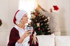 Attentive blonde waiting for party. Just relax. Silhouette of elderly men that standing in semi position on the background and decorating Christmas tree while stock images