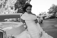 Bride poses with vintage car, black and white wedding photo royalty free stock images