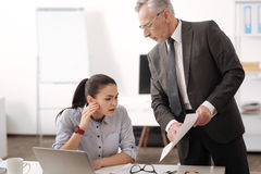 Attentive brunette looking at new documents. I see it. Serious gray-haired male person standing over secretary holding sheets of paper while looking downwards Stock Image