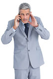 Attentive businessman answering phone Stock Image