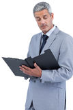 Attentive businessman holding clipboard Stock Images