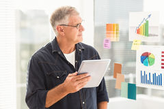 Attentive businessman looking flow charts on the wall. At office stock photo