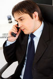 Attentive businessman talking on telephone. Attentive young business man talking on telephone in office Stock Image