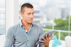 Attentive businessman watching at his tablet Stock Images