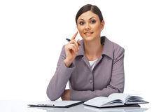 Attentive Businesswoman. Portrait of a young attentive businesswoman with a pen and dairy over white Royalty Free Stock Images