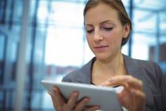 Attentive businesswoman using digital tablet in corridor Stock Photo