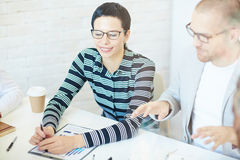 Attentive businesswoman. Young attentive businesswoman listening to colleague explanation stock photo