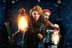 Attentive couple playing quest game while keeping hand lanterns against Christmas background. Couple outside with snow at night. Adventure. Alert couple with stock image
