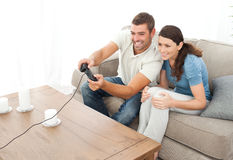Attentive couple playing video game together. In the living room at home Royalty Free Stock Photography