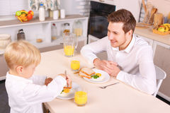 Attentive dad watches his son eating Stock Images