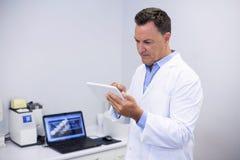 Attentive dentist using digital tablet Royalty Free Stock Image