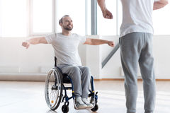 Attentive disabled man training in the gym with the orthopedist. My everyday physical therapy. Hardworking delighted positive disabled men repeating exercises stock photos