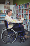 Attentive disabled school teacher reading book in library Stock Photo