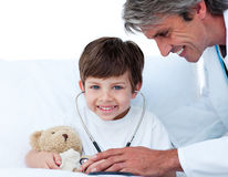 Attentive doctor playing with a little boy Royalty Free Stock Photos