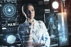 Attentive doctor touching her chin while thinking about the DNA analysis. DNA analysis. Smart calm experienced doctor standing with her fingers touching her chin Royalty Free Stock Image