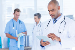 Attentive doctor using his tablet Stock Photography