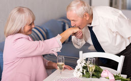 Attentive elderly man kissing his womans hand Stock Images