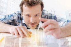 Attentive engineer using compasses. Perfect worker. Close up of attentive engineer using compasses while leaning on the table and working with sketch Royalty Free Stock Photo
