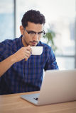 Attentive executive having coffee while using laptop at desk Stock Images