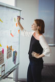 Attentive executive writing on sticky note Stock Photography