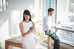 Attentive executives using mobile phone at desk Stock Photo