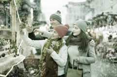 Attentive family couple with teen girl choosing Christmas decora Royalty Free Stock Photo