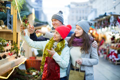 Attentive family couple with teen girl choosing Christmas decora Stock Photos