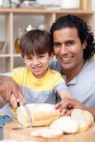 Attentive father helping his son cut some bread in. The kitchen Stock Photo