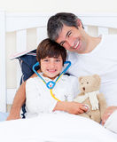 Attentive father and his sick son playing Royalty Free Stock Photos