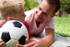 Attentive father and his son holding a soccer ball. Close-up of an attentive father and his son holding a soccer ball in a park Stock Photo