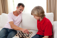 Attentive father playing chess with his son. At home Royalty Free Stock Photography