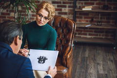 Attentive female advisor watching her patient. What do you see here. Serious women is sitting afore male client. He looking at inkblot on paper Stock Photo