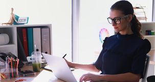 Female executive working at her desk in office 4k