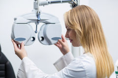 Attentive female optometrist adjusting phoropter Royalty Free Stock Photography