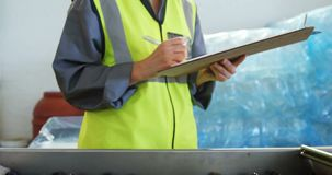 Female worker writing on clipboard in olive factory 4k stock footage