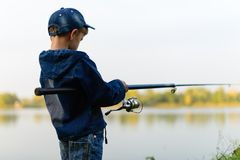 A fisherman boy on the river bank with a fishing rod in his hand Royalty Free Stock Photos