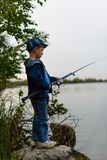 A fisherman boy on the river bank with a fishing rod in his hand. Attentive , focused, serious child is on a summer fishing on the river with a fishing rod in Stock Image