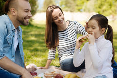 Attentive girl while eating tasty sandwich Royalty Free Stock Image