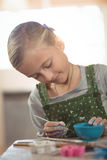 Attentive girl painting on bowl Royalty Free Stock Photo