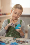 Attentive girl painting on bowl Stock Image