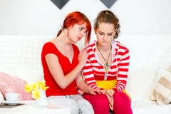 Attentive girl soothing her sad girlfriend. Attentive young girl sitting on sofa and soothing her sad girlfriend Stock Image